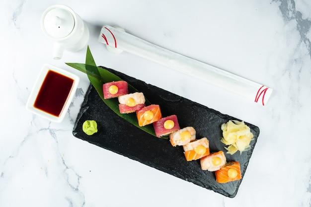 Coloque los rollos de sushi servidos sobre una hoja de plátano sobre una piedra negra sobre una mesa de mármol con palillos y salsa de soja. comida japonesa. sushi de salmón y atún con camarones. mariscos saludables.