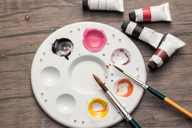 El color del agua y la placa de color mezclado y el pincel se colocan sobre la mesa de madera para dibujar arte en papel.