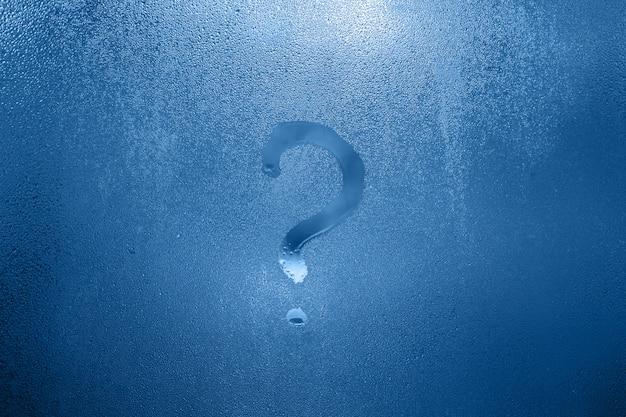 Color del año 2020 - azul clásico. lluvia, signo de interrogación en una ventana mojada
