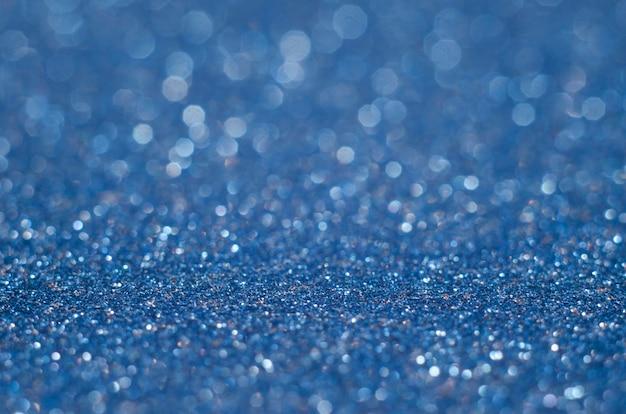 Color azul clásico. color del año 2020. fondo abstracto festivo bokeh con destellos brillantes desenfoque. macro de polvo brillante de brillos borrosos de cerca, copie el espacio para el logotipo de texto