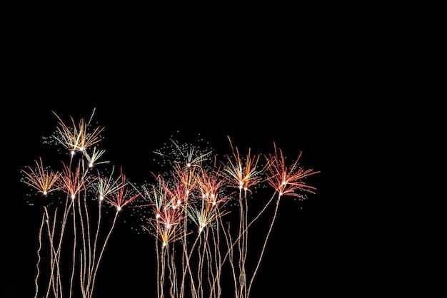 El color y la belleza de los fuegos artificiales, en el cielo negro por la noche, para celebrar el festival navideño, al concepto de feliz año nuevo.