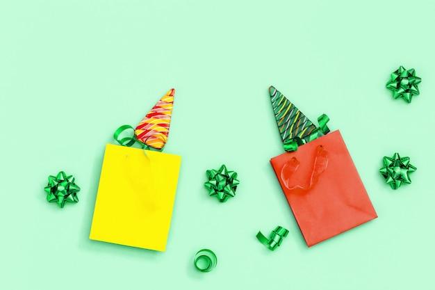 Color caramelo creativo para año nuevo o navidad. piruletas con forma de árbol de navidad en bolsa de regalo de papel sobre fondo de color neo mint.