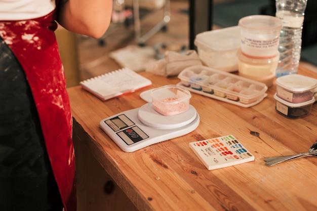 Color de cerámica en el recipiente sobre la escala de medición en el escritorio de madera