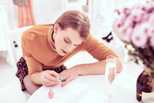 Uñas de color de niña. atractivo transgénero ordenado con atuendo provocativo y grandes joyerías y preparándose para la cita.