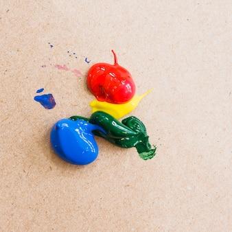 Color de pintura acrílica brillante sobre fondo de cartón con textura.