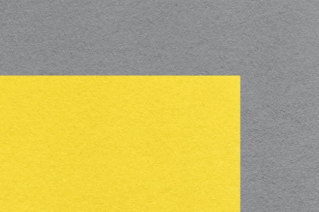 Color de tendencia pantone del año 2021 amarillo iluminado y gris definitivo. textura del viejo fondo de papel gris neutro, macro.