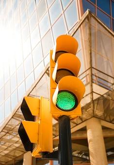 Color verde en el semáforo frente a edificio moderno.