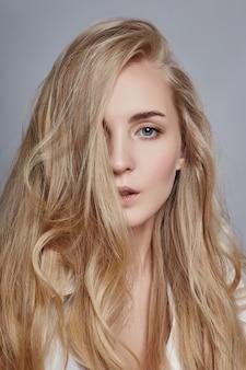 Coloración de cabello largo de mujer hermosa en ultra rubio, maquillaje natural. rizos de peinado con estilo realizados en un salón de belleza. chica rubia de moda