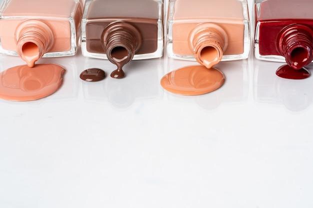 Colores desnudos esmalte de uñas derramado sobre fondo blanco