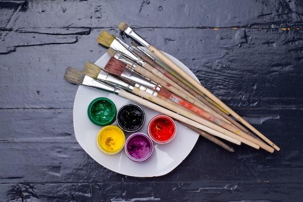 Colores en los frascos, pinceles y una paleta.