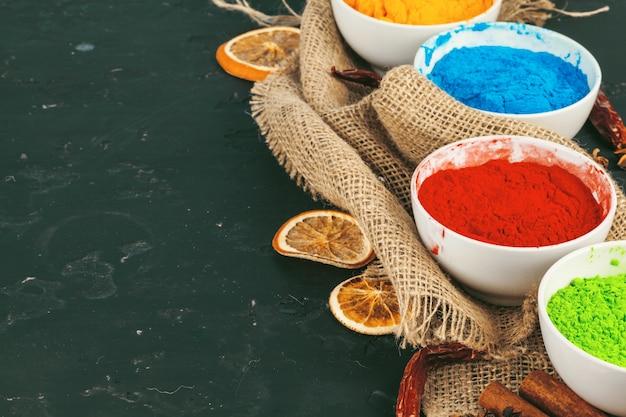 Colores de holi indio tradicional en polvo, especias en rústico oscuro
