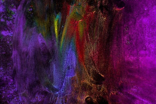 Colores holi multicolores manchados con mano sobre fondo negro