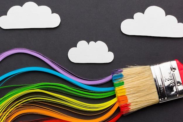 Colores ondulados y pincel con nubes