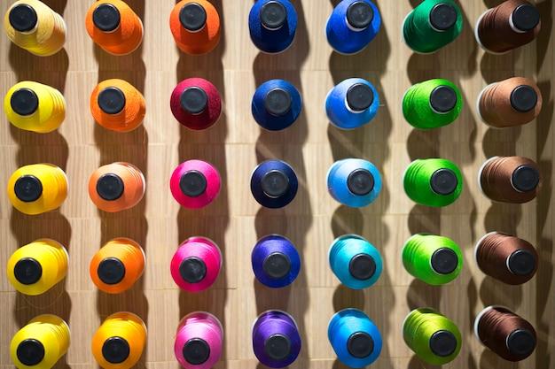 Colores surtidos de hilo en carretes. proceso de bordado en la fábrica.