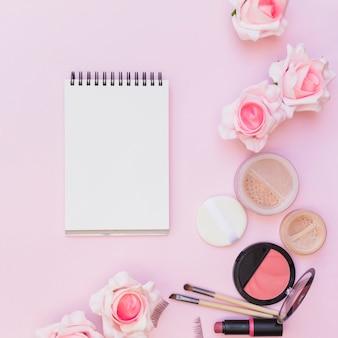 Colorete; lápiz labial; esponja; pincel de maquillaje con rosas sobre fondo rosa