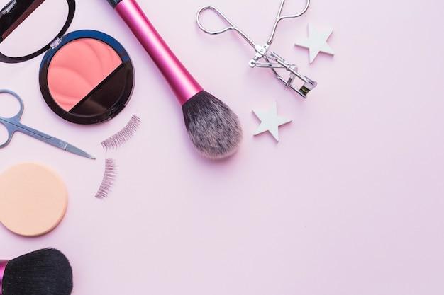 Colorete rosa; esponja; tijeras; pestañas; rizador de pestañas y pincel de maquillaje sobre fondo rosa