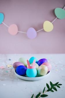 Colorfil huevo de pascua, rosa, verde, azul, dorado con orejas de conejo sobre fondo de mármol
