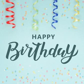 Colorfu serpentina de decoración festiva y confeti sobre fondo azul. letras de feliz cumpleaños.