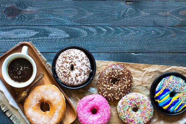 Colorida composición de desayuno donuts con laptop y taza de café