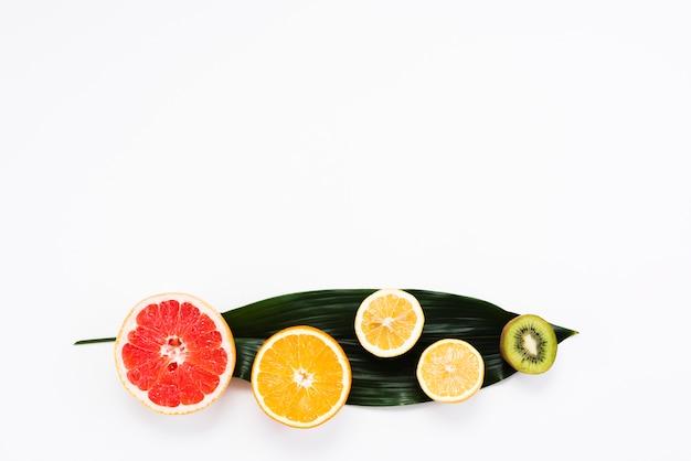 Colorida composición de frutas exóticas en hoja de plátano.