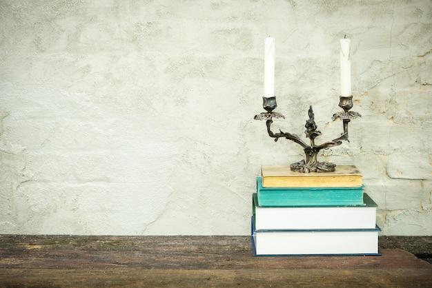 Colorida composición con libros antiguos de época, diario en mesa de cubierta de madera y concreto beige