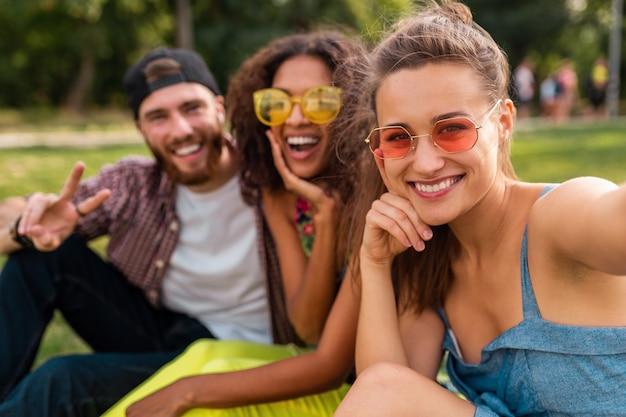 Colorida y elegante compañía joven feliz de amigos sentados en el parque, hombres y mujeres que se divierten juntos