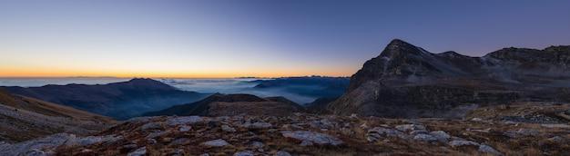Colorida luz del sol detrás de majestuosas cumbres en italia