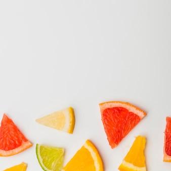 Colorida rebanada triangular de pomelos; limón y una naranja sobre fondo blanco