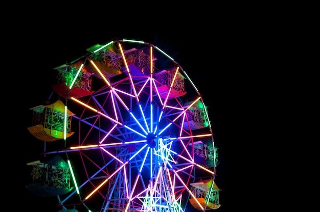 Colorida rueda de la fortuna en una hermosa noche