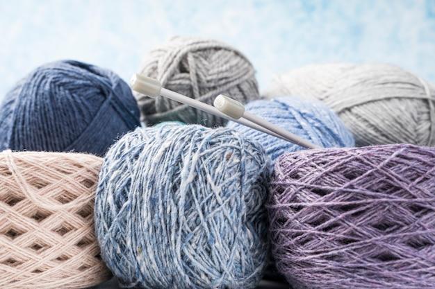 Coloridas bolas de lana con agujas de plástico.
