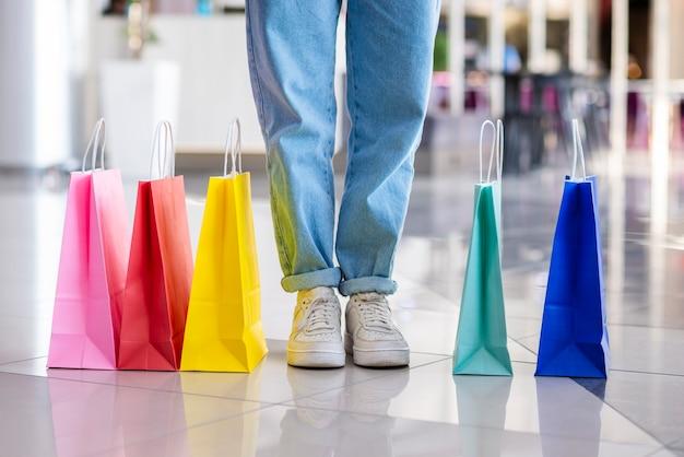 Coloridas bolsas de compras cerca de las piernas