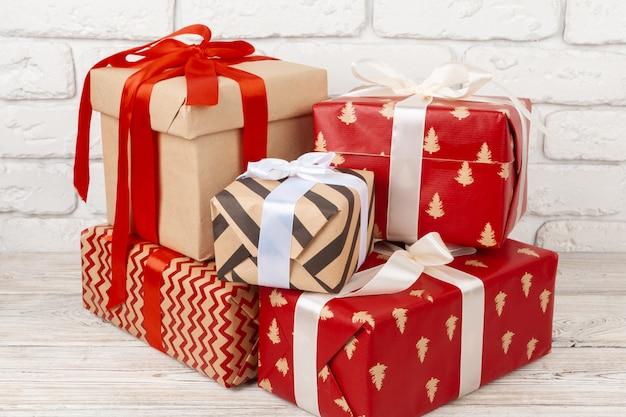 Coloridas cajas de regalo sobre fondo de pared de ladrillo blanco