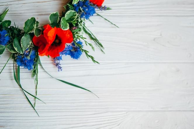 Coloridas flores artificiales decorativas sobre fondo de madera