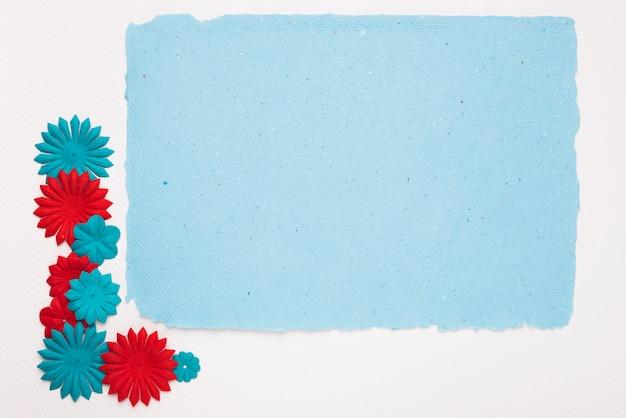 Coloridas flores cerca del marco azul aislado en el fondo