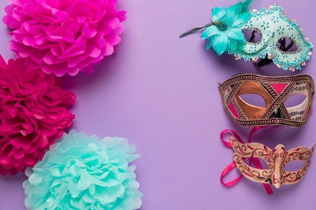 Coloridas flores de papel con máscaras de carnaval