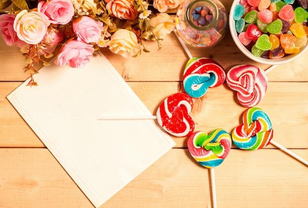 Coloridas flores rosas y etiqueta vacía para su texto con gelatina dulce, sabor a fruta, tono de color pastel en forma de corazón de caramelo sobre fondo de madera