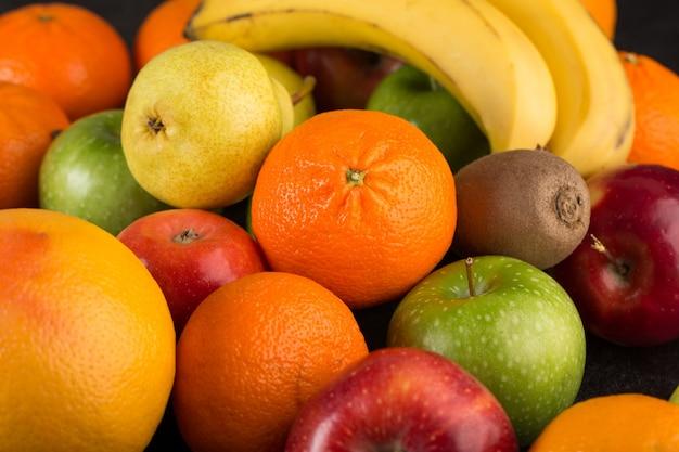 Coloridas frutas maduras suaves naranjas frescas y manzanas en el escritorio oscuro