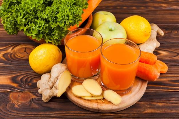 Coloridas frutas y verduras con jugo en la mesa
