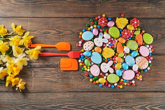 Coloridas galletas de pascua y espátulas sobre la mesa.