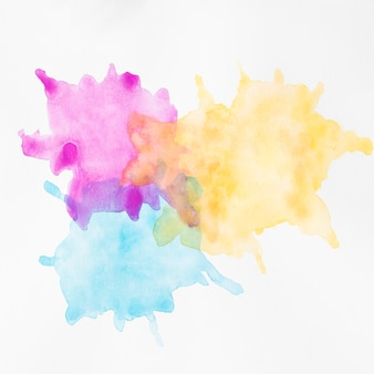 Coloridas manchas pintadas a mano sobre superficie blanca