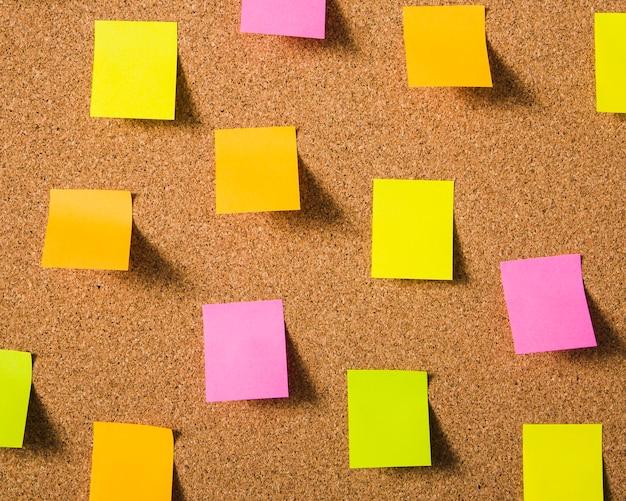 Coloridas notas adhesivas en blanco sobre tablero de corcho