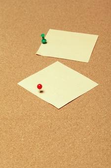 Coloridas notas adhesivas con chinchetas y espacio en blanco en corcho
