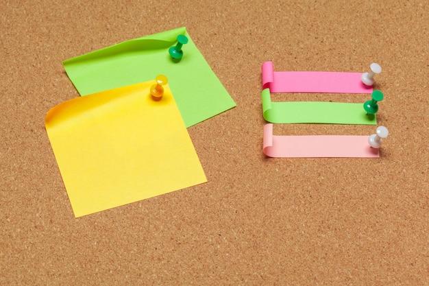 Coloridas notas adhesivas con chinchetas en la superficie del corcho