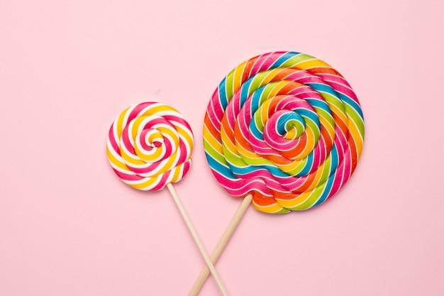 Coloridas paletas en espiral con palo de madera en rosa