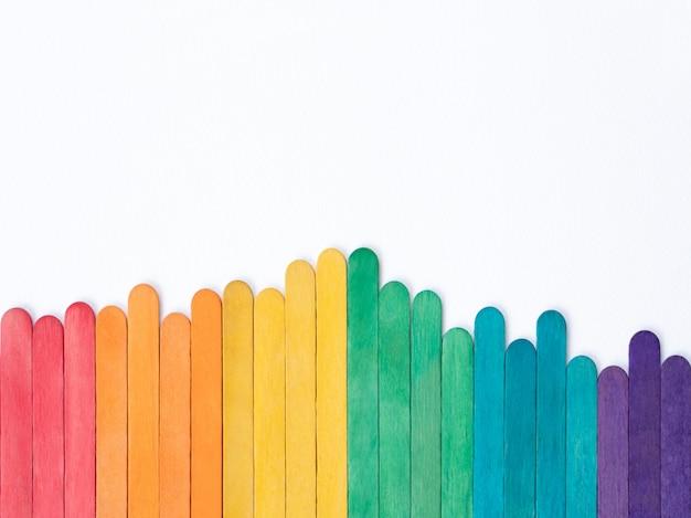 Coloridas paletas de madera de arco iris sobre papel blanco con espacio de copia, marco de cubierta de palos de colores abstractos para obras de arte artesanales para niños, concepto de regreso a la escuela para niños