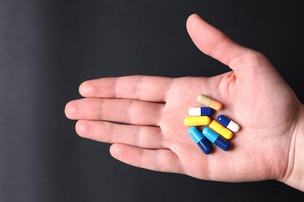 Coloridas píldoras médicas en la mano de una persona.