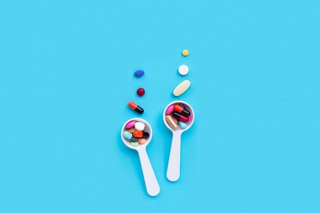 Coloridas píldoras de medicina, tabletas y cápsulas sobre fondo azul.