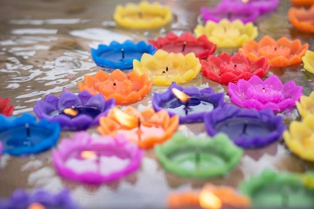 Coloridas velas en forma de flor están flotando en el agua.