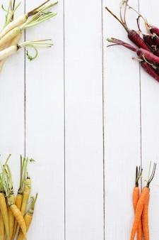 Coloridas zanahorias en el fondo de la mesa de madera