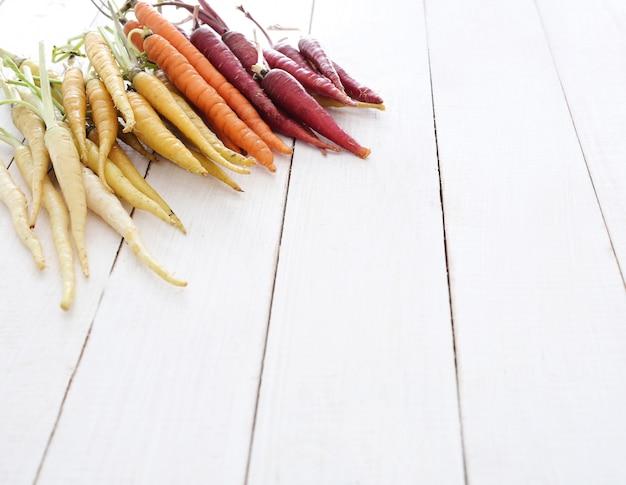 Coloridas zanahorias en mesa de madera